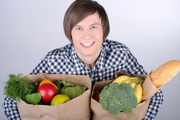 買い物袋を持って笑顔の若い男。