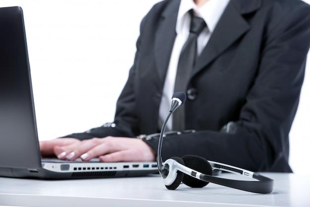 Девушка сидит за компьютером наушники на столе.