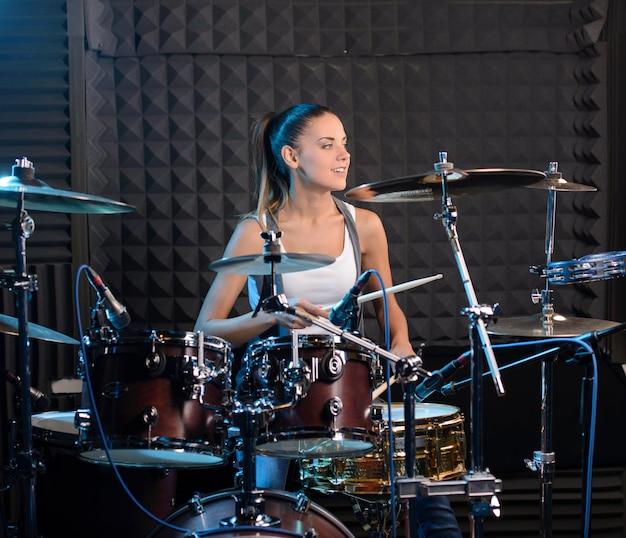 Девушка за барабанной установкой в профессиональной студии.