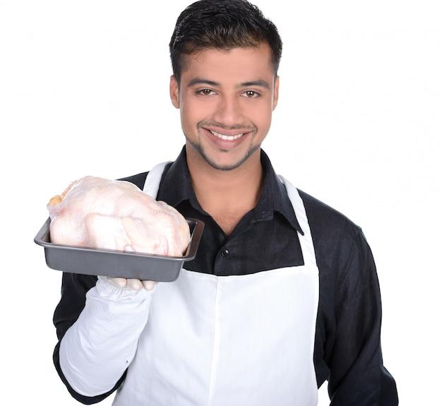 Молодой красивый мужчина держит курицу.
