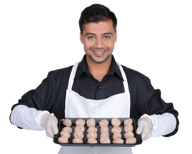 Профессиональный мясник держит красное мясо.