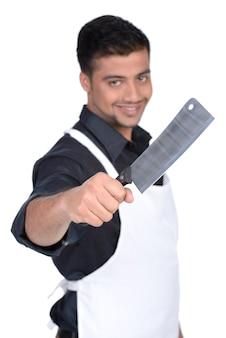 Красивый мясник, улыбаясь и держа нож в руке.