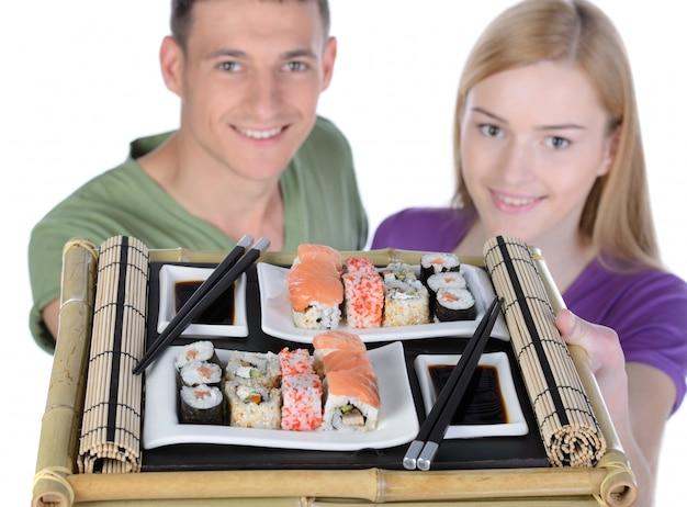 カップルがお互いの近くに座って寿司を食べる。