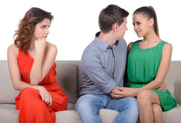 嫉妬。ソファに座っている若い悲しい女性。