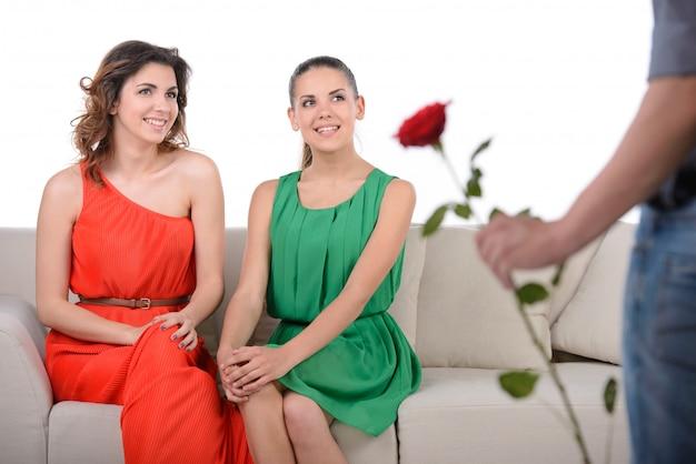 Мужчина выбирает между двумя девушками подарок на цветок.
