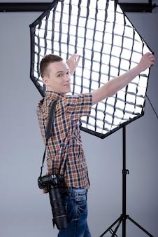 彼のスタジオでプロのデジタルカメラを持つ写真家。