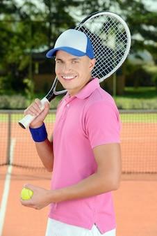 テニス選手がテニスコートの前でポーズします。
