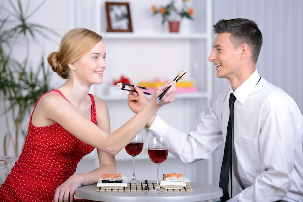 レストランで一緒に座っている美しい若いカップル。