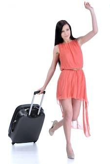 トラベルバッグと一緒にカジュアルウォーキングをする女性の全身像。