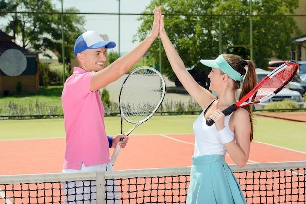 Мужчина и девушка после игры дают друг другу пять.