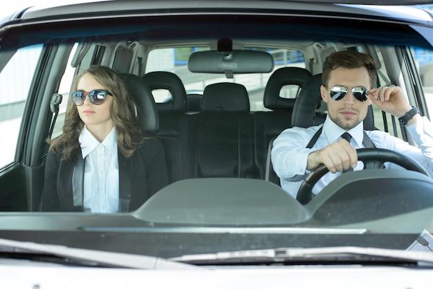 ビジネスマンは車の後ろに座って行きます。