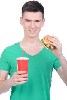 Молодой человек ест фаст-фуд, изолированные на белом