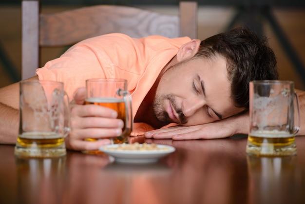 Пьяный мужчина сидит в пабе с закрытыми глазами.