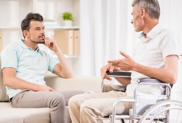 大人の男が家で座っていると彼の長老の父親に話しています。
