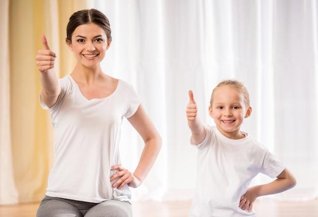 Люди делают упражнения йоги дома.