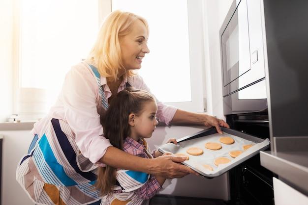 祖母は女の子に自家製クッキーを作るように教えます。