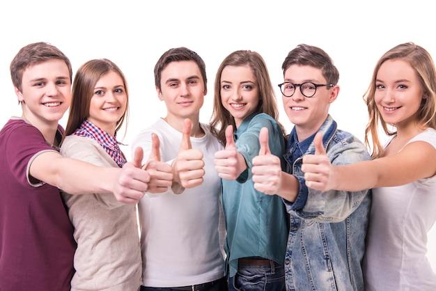 Счастливый улыбающийся молодой группы друзей с большими пальцами руки вверх.