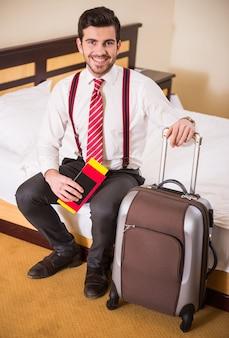 男がベッドに座り、荷物を抱えています。