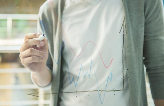 創造的な男が事務所の窓で事業戦略を描きます。