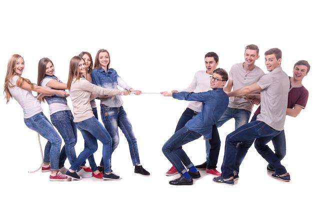 Мужчины и девушки тянут веревку друг на друга.