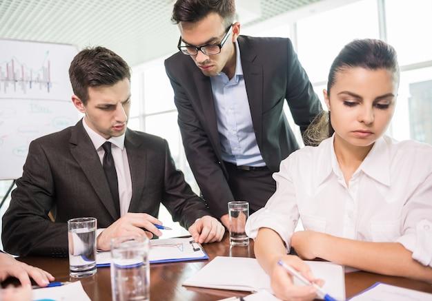 オフィスの会議室に座っていると働いている人々。