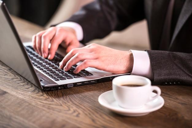 Крупный план. бизнесмен работает на ноутбуке с чашкой кофе.