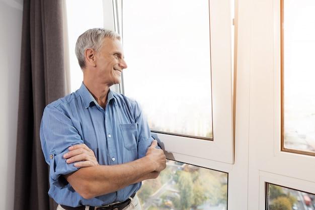 大きな窓の近くの老人。幸せな男性の笑みを浮かべてください。