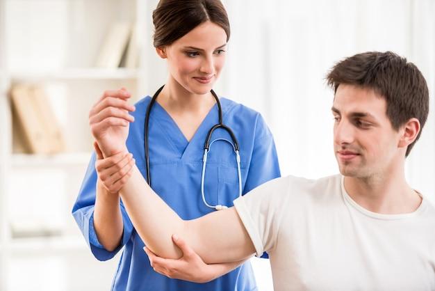Физиотерапевт, массируя руку пациента мужского пола.