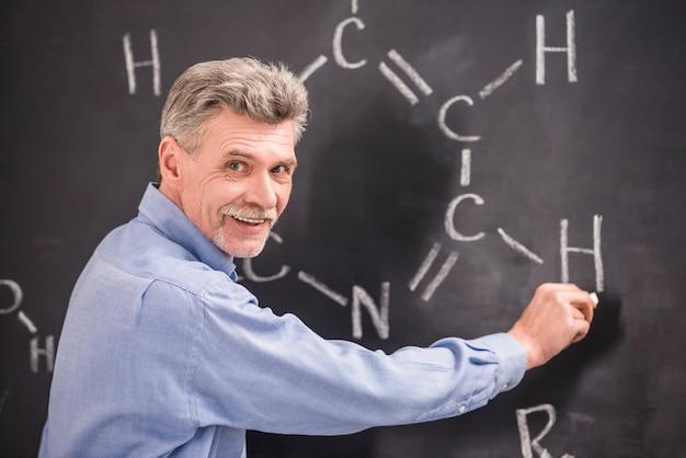 Химия пишет на доске формула в университете.