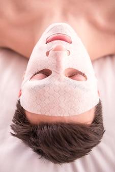 Азиатская девушка лежит на кровати в маске.