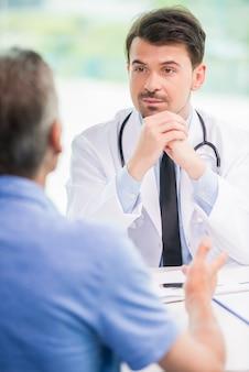 彼のオフィスで患者と話している深刻なハンサムな医者。