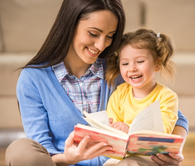 魅力的な母親は本の中で画像を見せています。