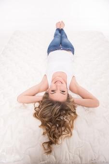 笑顔の若い女性は、品質のマットレスの上に横たわっています。