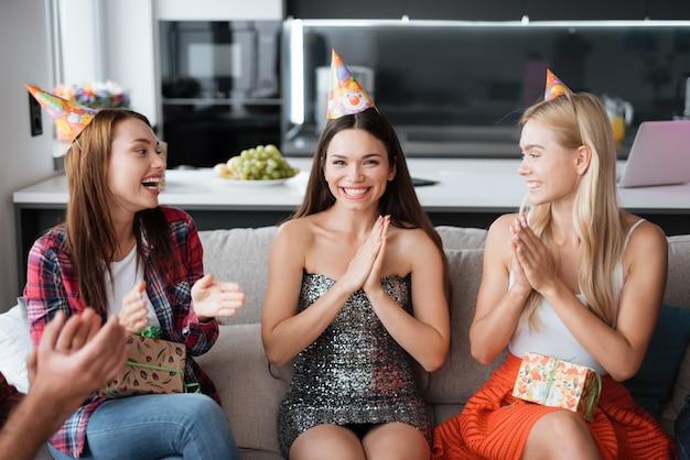 誕生日帽子の誕生日の女の子。ゲストの笑顔