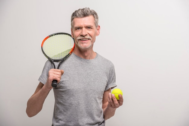 Старший мужской тренер с теннисной ракеткой и теннисным мячом.