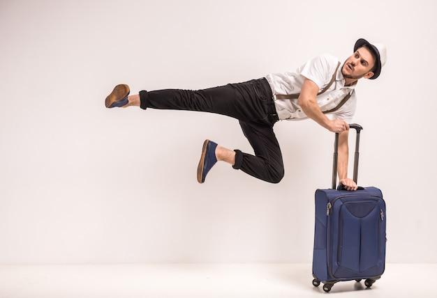 創造的な男は灰色のスーツケースとポーズします。