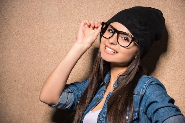 長い毛を持つメガネの若い美しさブルネットの少女。