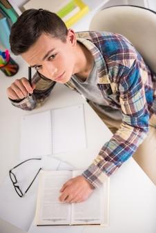 テーブルに座っていると宿題をしているティーンエイジャーの平面図です。