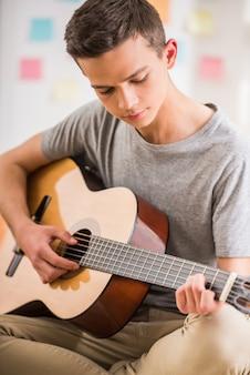 男性のティーンエイジャーは家で座っているとギターを弾きます。