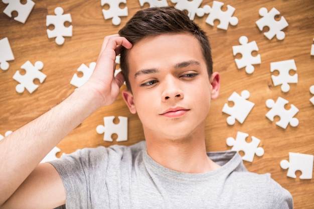 Взгляд сверху подростка лежа на поле дома с головоломками.