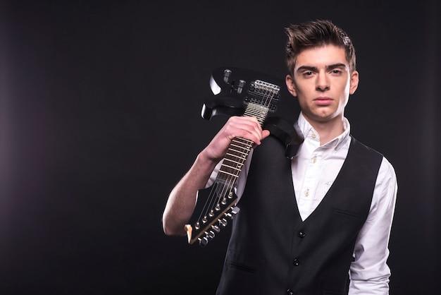 エレキギターを持つ若いギタリスト。