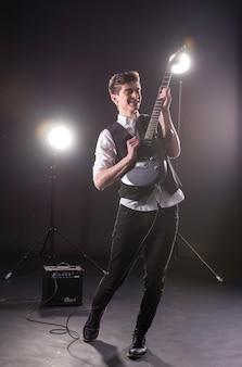 暗闇の中でエレキギターを持つ若いギタリスト