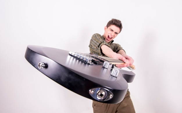 スタジオでエレキギターを持つ若いギタリスト。