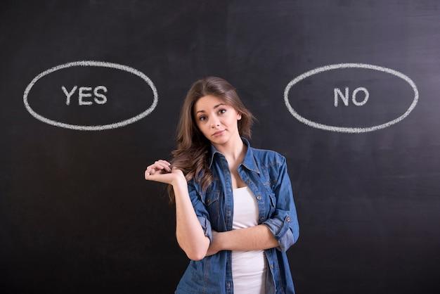 Женщина стоит на черном фоне и думает: да или нет.