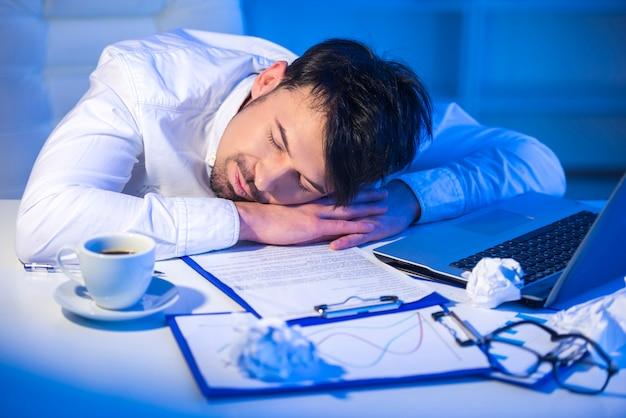 コンピューターで仕事で寝ている疲れた男。