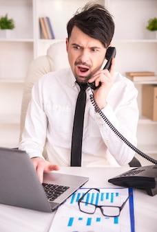 Злой бизнесмен работает на ноутбуке и разговаривает по телефону