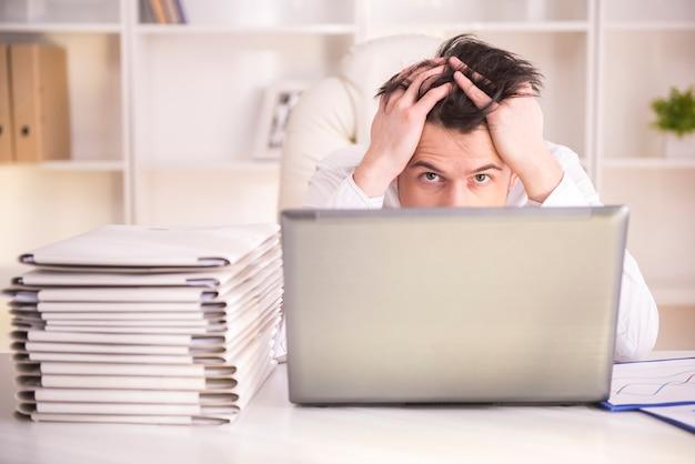 オフィスの机に座っている欲求不満の中年実業家。