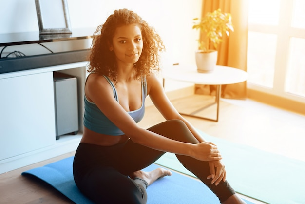 Афро американская девушка сидит на ковре йоги дома