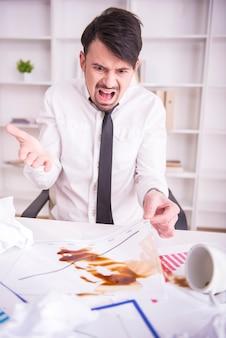 ビジネスマンのドキュメントにこぼれたコーヒーに怒っています。