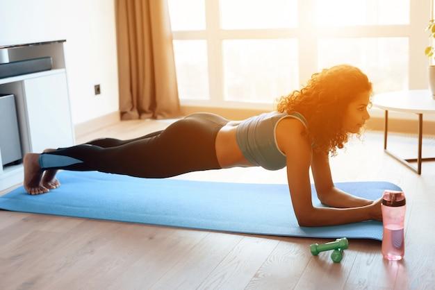 Красивая африканская девушка делая тренировки йоги на циновке йоги.